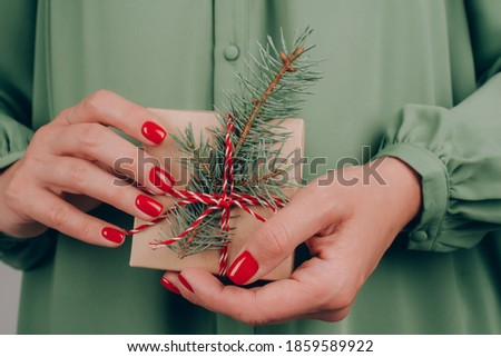 Young woman wearing green dress holding Christmas present box decorated with Christmas tree twig. Christmas holidays and New Year celebration concept. Preparing family gifts for Christmas Royalty-Free Stock Photo #1859589922