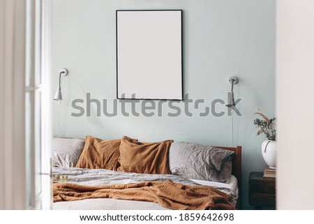 Portrait black picture frame mockup on sage green wall. Bedroom view through open white  door. Grey linen and rusty muslin pillows on wooden bed. Scandinavian interior. Ceramic vase with dry grass.