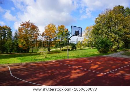 A basketball hoop in a park on a sunny autumn day - city park