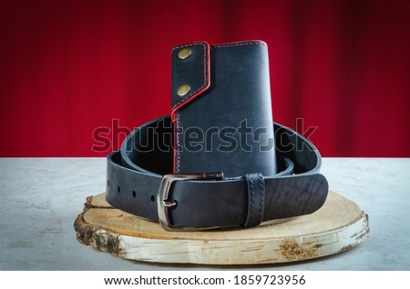 Men's wallet longer made of genuine black leather handmade on a birch cut is wrapped in a classic men's leather belt Royalty-Free Stock Photo #1859723956