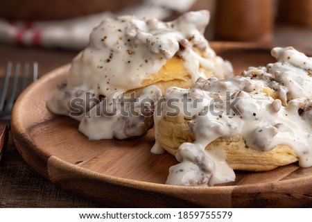 Closeup of biscuits and creamy sausage gravy on a wooden plate  Royalty-Free Stock Photo #1859755579