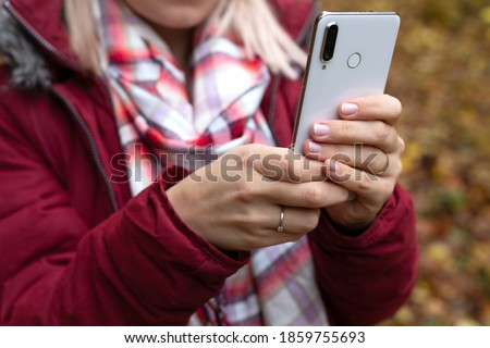 Close up picture of female hands holding smartphone, taking picture outdoor, autumn background