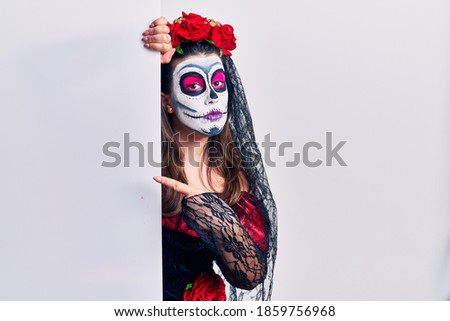 Young woman wearing day of the dead custome holding blank empty banner pointing with hand finger to the side showing advertisement, serious and calm face