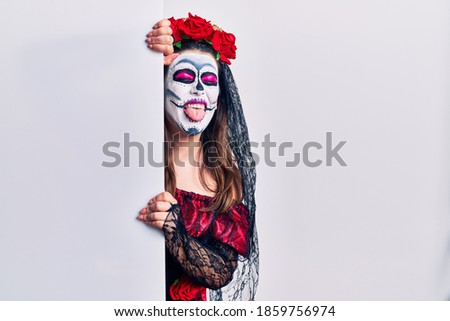 Young woman wearing day of the dead custome holding blank empty banner sticking tongue out happy with funny expression. emotion concept.