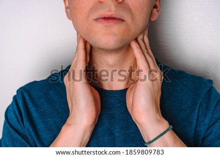 A man checks the lymph nodes on his neck. Royalty-Free Stock Photo #1859809783