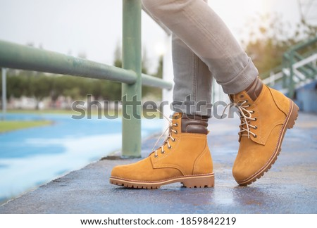 Men fashion in leather boots, Close up view on man's legs in gray jeans and yellow leather boots. Royalty-Free Stock Photo #1859842219