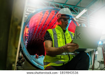 Chief Industrial Engineer in Hard Hats used Laptop Computer check and control machine while Sitting in the Heavy Industry Manufacturing Factory.man at work and maintenance engineer concept. Royalty-Free Stock Photo #1859843536