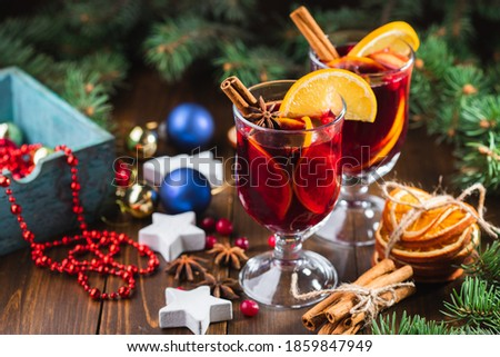 Hot wine drink with spices and fruits in a tall glass and a box with toys for the Christmas tree on the background. Fragrant, hot punch or mulled wine for Christmas. #1859847949