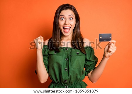 Photo of lucky impressed lady dressed green off-shoulders blouse arm fist holding credit card isolated orange color background
