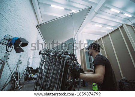 Illuminators with lighting equipment, lighting devices on the set. Lighting production for filming movies, advertising, TV series. Modern photography technique.