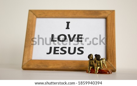 Wooden picture frame with inscription 'I love Jesus' on beautiful white background. Two bronze angeles on the table. Copy space.