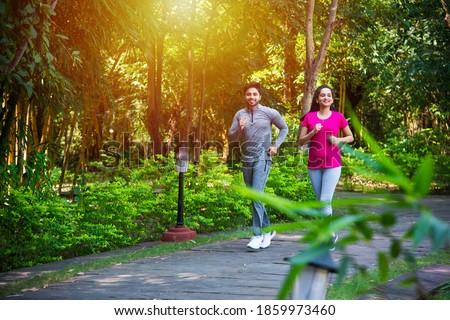 Indian asian young Couple jogging, running, exercising or stretching outdoors in park or nature Royalty-Free Stock Photo #1859973460