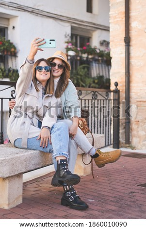 Two young beautiful smiling hipster female in trendy autumn clothes.Sexy carefree women sitting on the bench on the street in sunglasses. They taking selfie self portrait photos on smartphone.