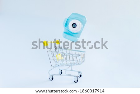 Blue photocamera falling in shopping cart on white backround. Electronics and photographic equipment shopping concept