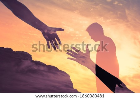 Young depressed man with head down feeling weak and some one reaching out to give him a helping hand.  Royalty-Free Stock Photo #1860060481