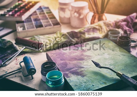Artistic equipment - canvas and palette knife, paint brushes, multicolored paints in artist studio. Royalty-Free Stock Photo #1860075139