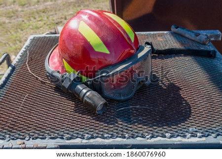 Firefighter helmet with flashlight, close-up.