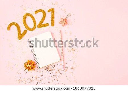 New Year goal list 2021. Desk with notebook for writing about plan listing of new year goals and resolutions setting on pink pastel background with star confetti. Change and determination concept. #1860079825