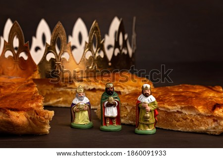 King cake or galette des rois in French. Traditional epiphany pie with golden paper crown and tiny charms Royalty-Free Stock Photo #1860091933