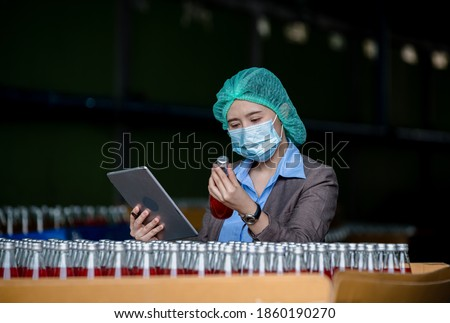 Worker of science in bottle beverage factory wearing safety  hat and face mask working to check quality of drink Basil seed produce on conveyer belt before distribution to market business. Royalty-Free Stock Photo #1860190270