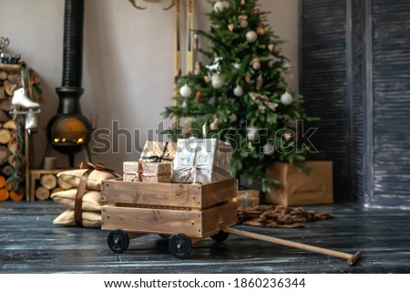 Christmas decorated fireplace and gifts in cozy Chalet. fire in stone furnace, wood in woodpile, white skates hanging on a wooden shelf. New year and Christmas interior-blurred background. Copy space.