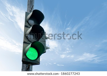 Traffic light in green color, with a blue sky and cloud in the background.