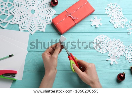 Woman making paper snowflake at turquoise wooden table, top view