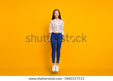 Full length photo portrait of cute gorgeous woman jumping up isolated on bright yellow colored background