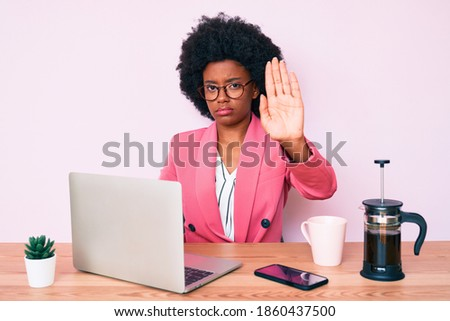 Young african american woman working at desk using computer laptop with open hand doing stop sign with serious and confident expression, defense gesture