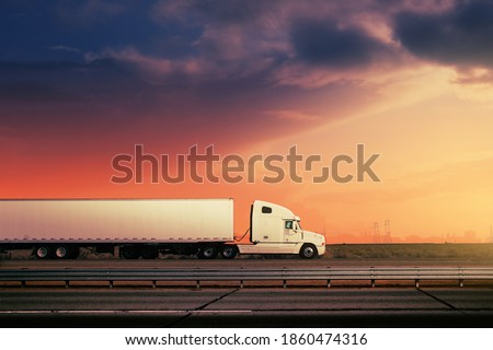 White freight truck driving on freeway road under red sunset sky. Royalty-Free Stock Photo #1860474316