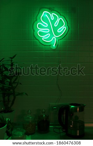 Neon sign monstera in the decor of the kitchen. Trendy style. Neon sign. Custom neon. Home decor.