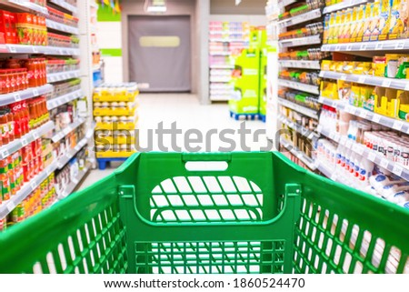 close up and first person or pov view of a cart buying products and food in a empty supermarket Royalty-Free Stock Photo #1860524470