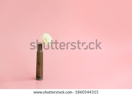 White chrysanthemum flower in an empty cartridge case from under a firearm on a pink background Royalty-Free Stock Photo #1860544315