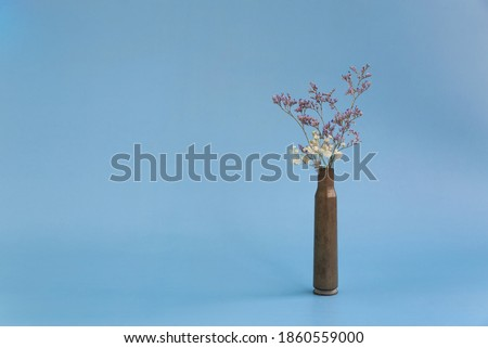 Dried flowers in an empty case from under a firearm on a blue background. Royalty-Free Stock Photo #1860559000