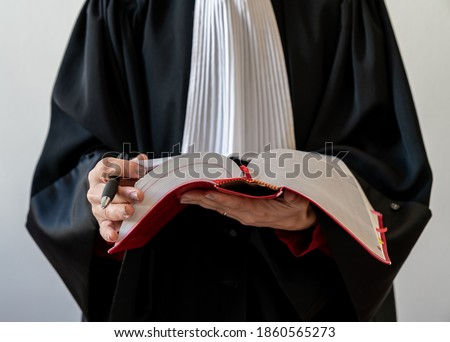 Justice, lawyer holding and reading open red law book - Translate French Penal Code red Book Royalty-Free Stock Photo #1860565273