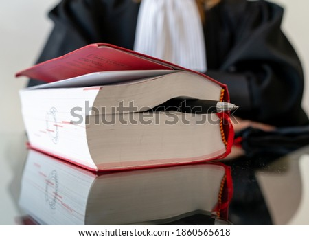 Justice, lawyer holding and reading open red law book - Translate French Penal Code law book Royalty-Free Stock Photo #1860565618