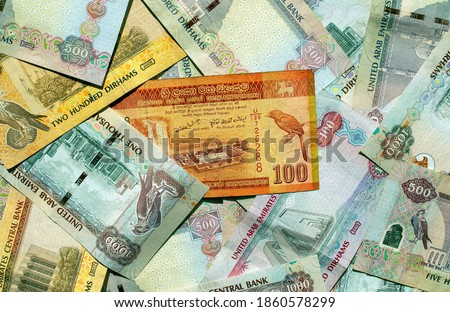 Sri Lankan rupee on top of UAE national currency, top view of mixed dirhams banknotes. AED and LKR money banknotes background. Exchange rate.