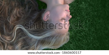 a close-up portrait of a beautiful young girl with long blonde hair, eyes closed, lying upside down on the green grass