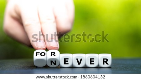 Hand turns dice and changes the word never to forever.