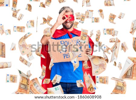 Young blond man wearing super hero custome holding power to the people cardboard banner smiling happy doing ok sign with hand on eye looking through fingers