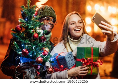 Portrait of happy smiling mixed-races couple taking funny selfie photos on mobile phone on street with little christmas tree. Man and woman taking pictures at night on new years eve. Magic time.