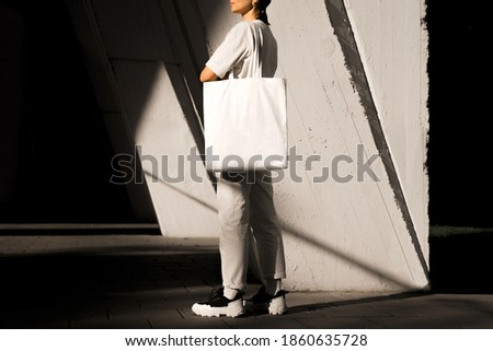 Girl holding white tote bag, template can be used for your design Royalty-Free Stock Photo #1860635728