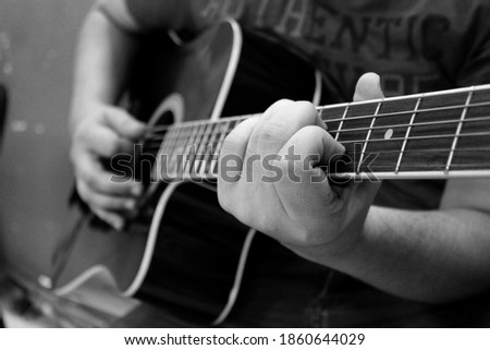 black and white pic of playing acoustic guitar