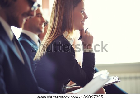 Row of business people making notes at seminar, focus on attentive young female Royalty-Free Stock Photo #186067295