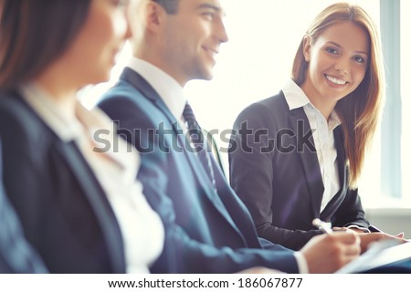 Smiling businesswoman looking at camera at seminar with her colleagues near by Royalty-Free Stock Photo #186067877
