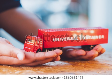 Closeup hand hold the red truck universal container using for logistics and business concept