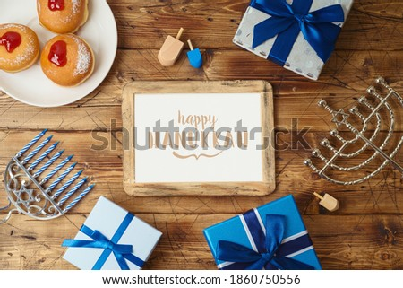 Jewish holiday Hanukkah greeting card with photo frame, traditional donuts, menorah and gift box on wooden background