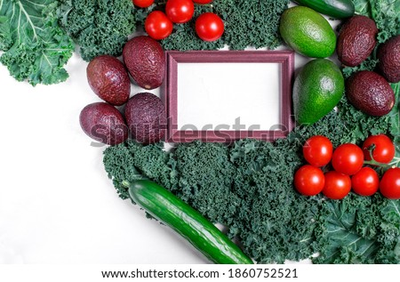 Vegetable assortment around the picture frame with copy space. Healthy food flat lay. Kale, avocado of two sorts, cherry tomato and cucumbers