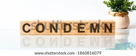 Wooden Blocks with the text: condemn. The text is written in black letters and is reflected in the mirror surface of the table. Front view concepts, flower in the background. Royalty-Free Stock Photo #1860816079