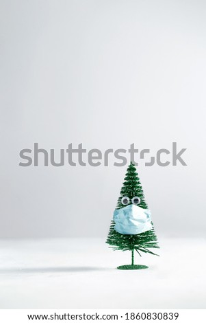 Pandemic concept holiday green Christmas tree with eyes wearing a surgical mask holiday